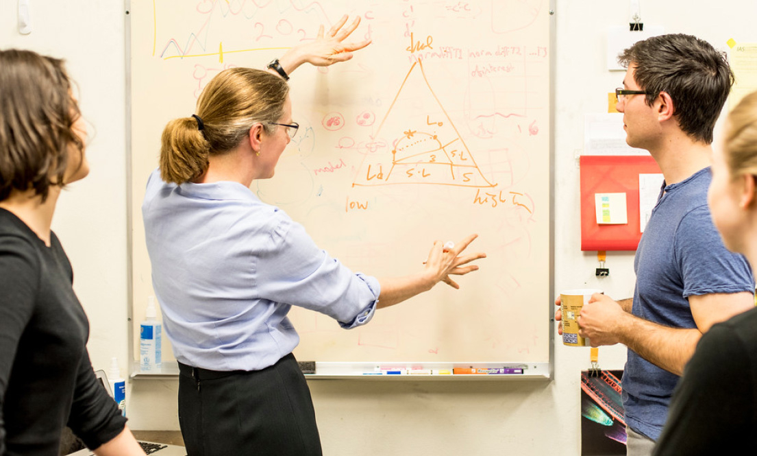 Faculty in discussion with students in front of whiteboard