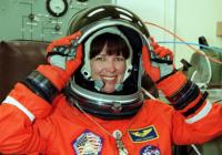 Janet Kavandi in an orange space suit lifting the visor of her helmet