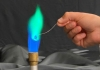 A graduate student demonstrates putting a copper chloride solution into a flame for the Atomic Emissions lab in CHEM 142.
